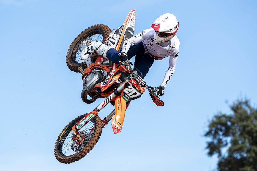 man in white and orange motocross suit riding motocross dirt bike