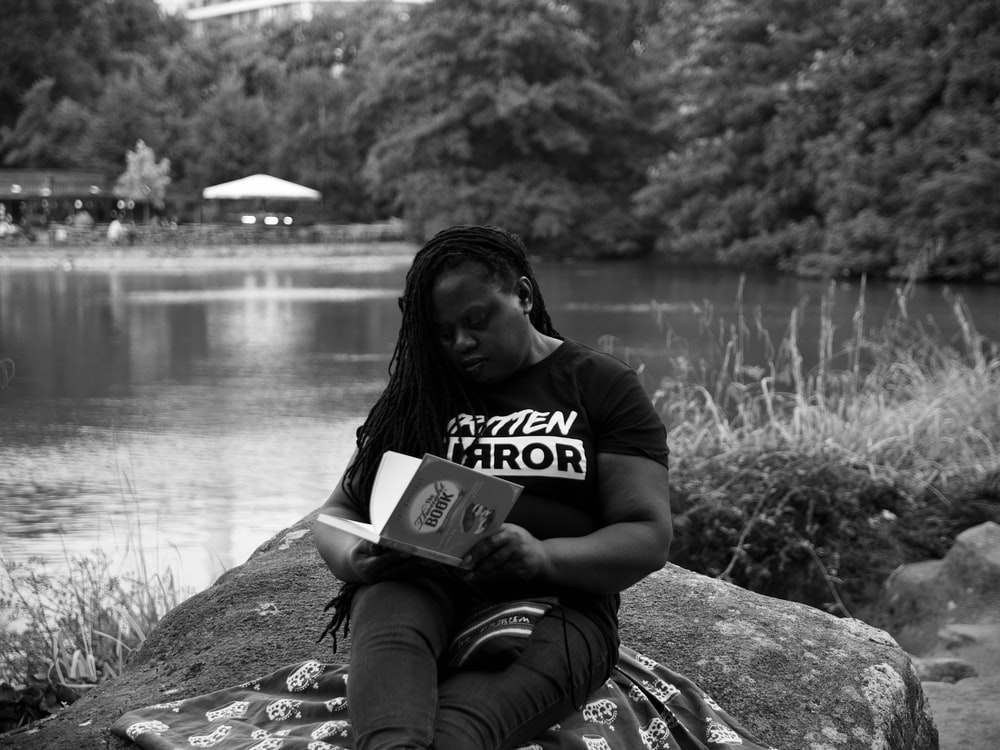 man in black t-shirt sitting on rock near body of water