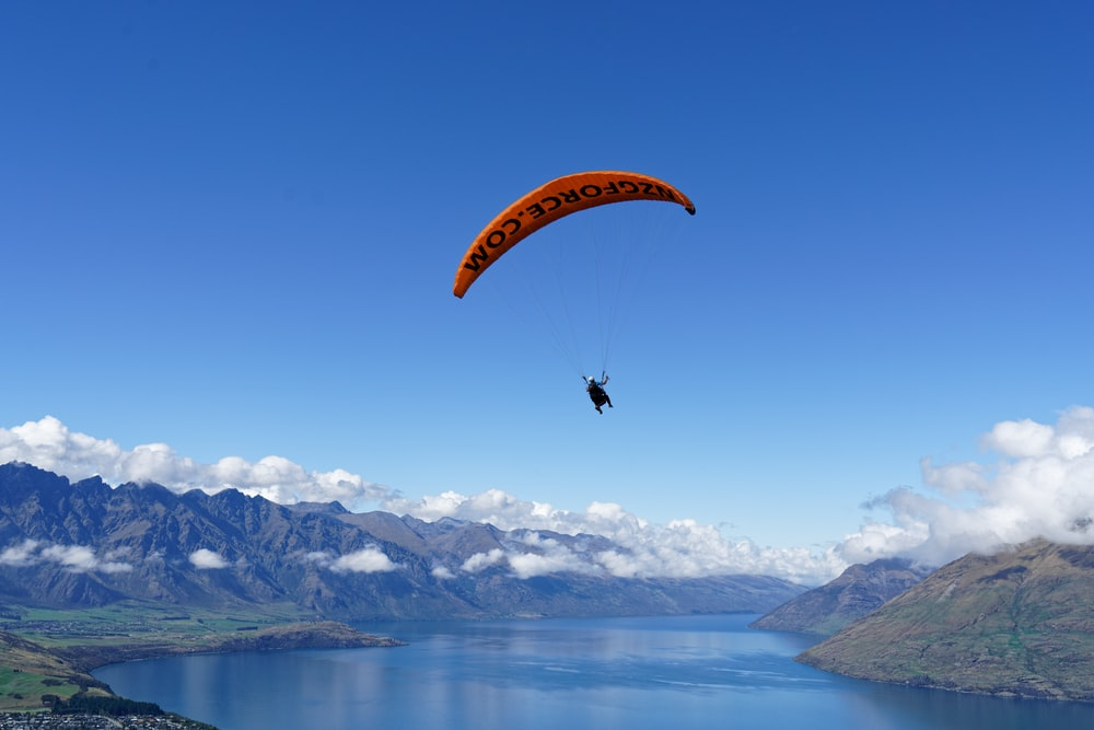 person in parachute over snow covered mountains during daytime