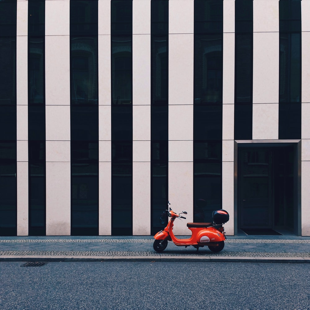 orange and black motor scooter parked beside white and gray concrete building during daytime