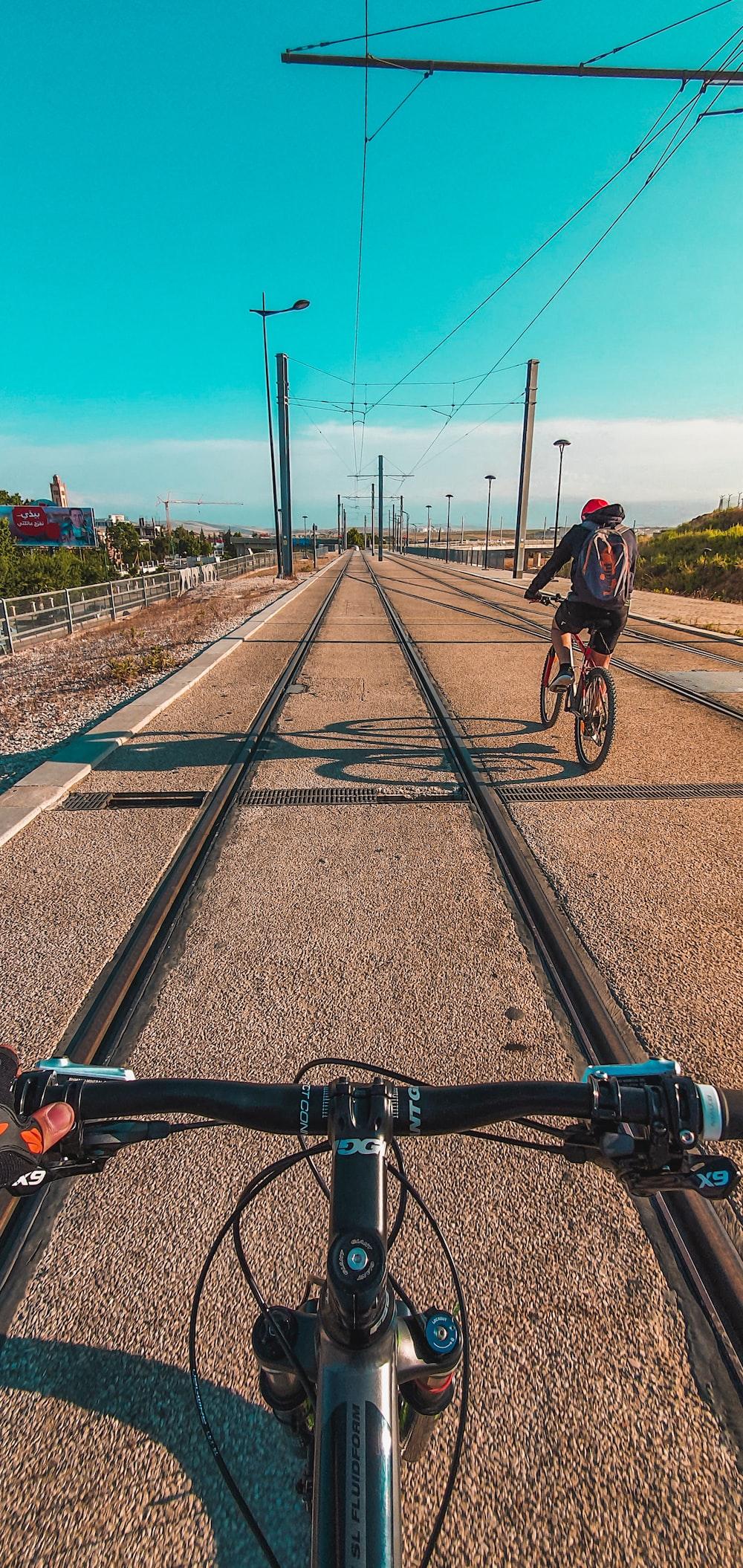 man in black jacket riding bicycle on train rail during daytime