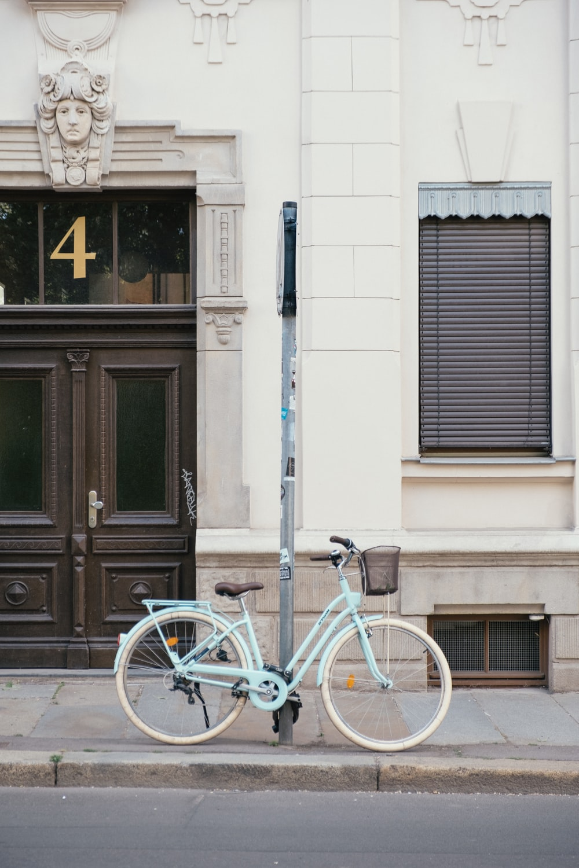 blue city bike parked beside black wooden door