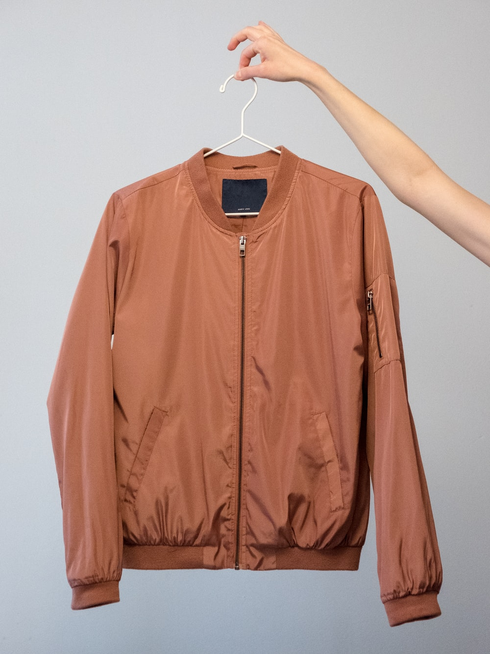 brown long sleeve shirt on white clothes hanger