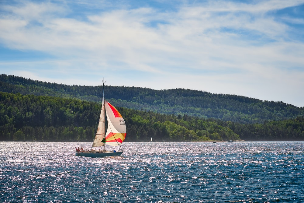 white sailboat on sea near green trees under white clouds during daytime