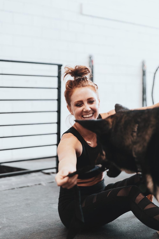 girl in pink t-shirt hugging black short coated dog