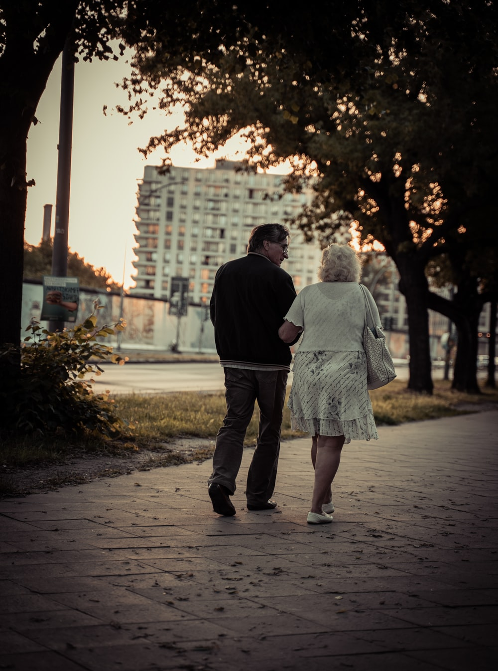 couple walking on sidewalk during daytime