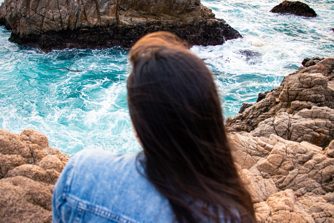 Brunette girl with jean jacket looking at the ocean while sitting on the edge of a rocky cliff.  Instagram | @jordanniranjan