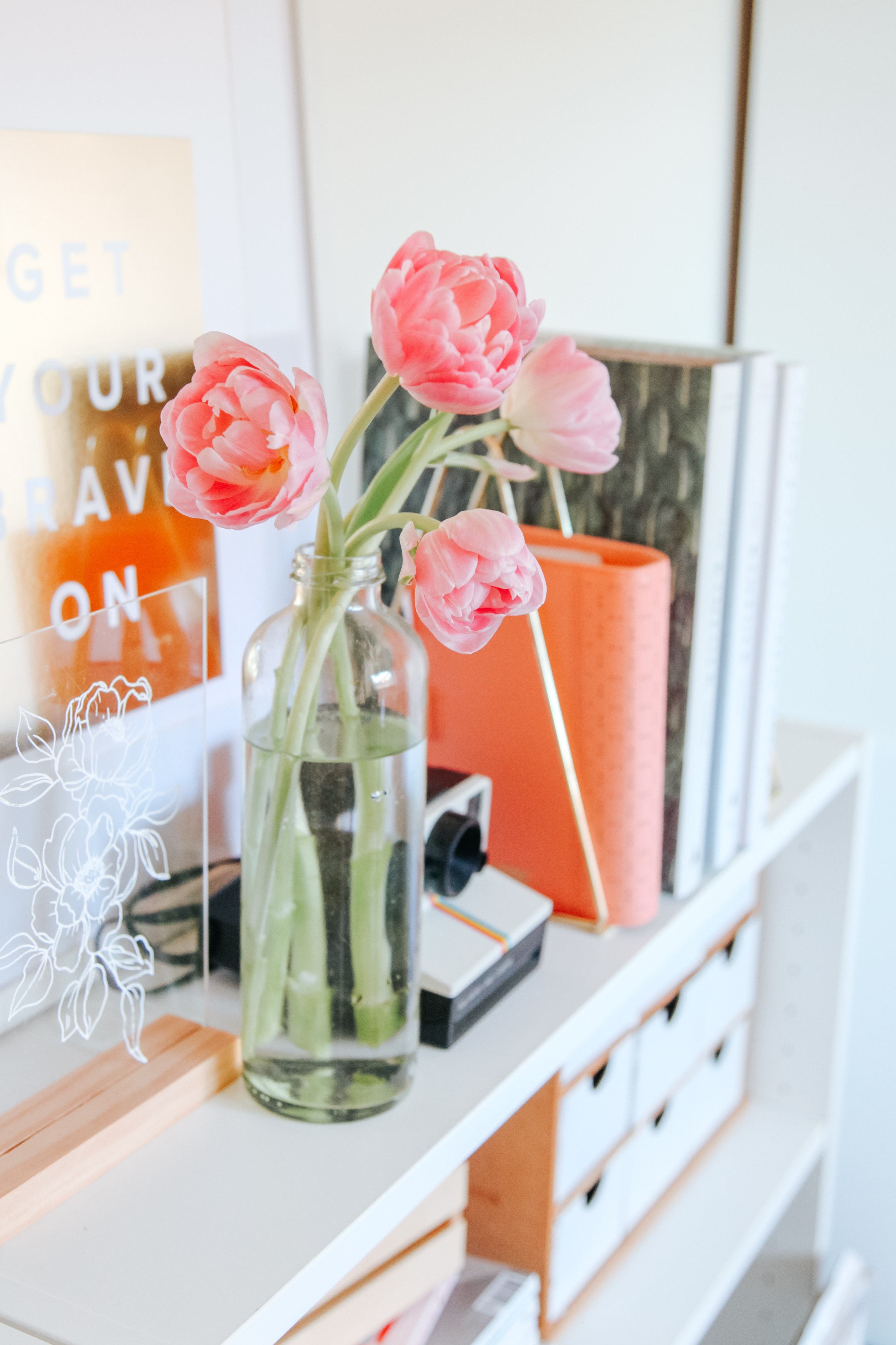 Pink pastel tulips in a glass vase on a shelf