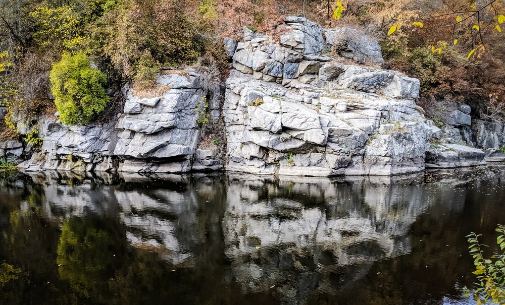 gray rock formation beside body of water during daytime