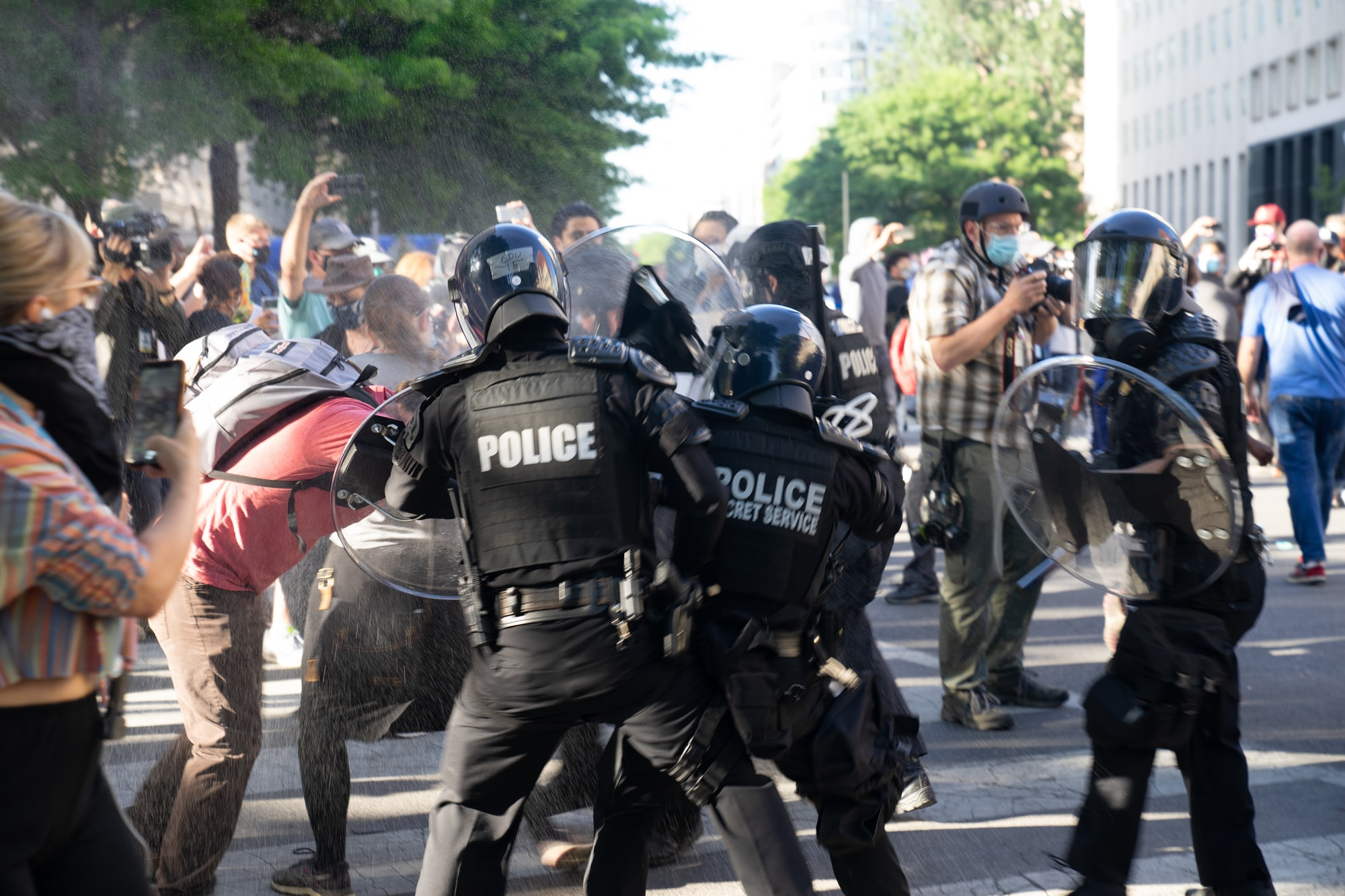 Riot police attacking peaceful protesters wearing masks