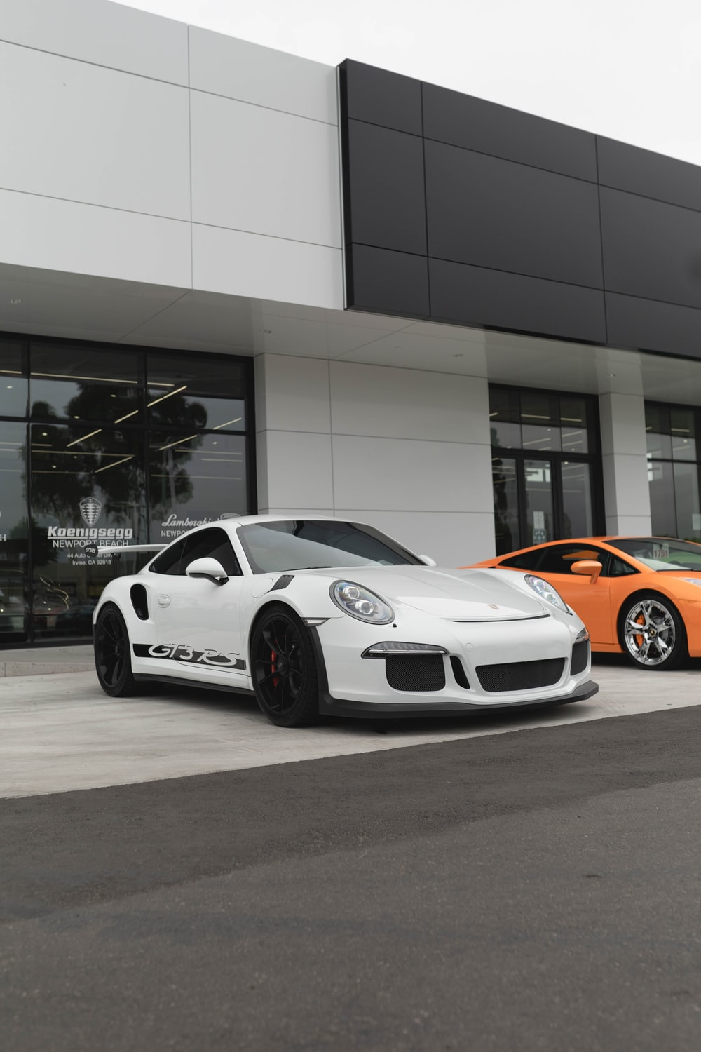 white and orange porsche 911 parked in front of white building
