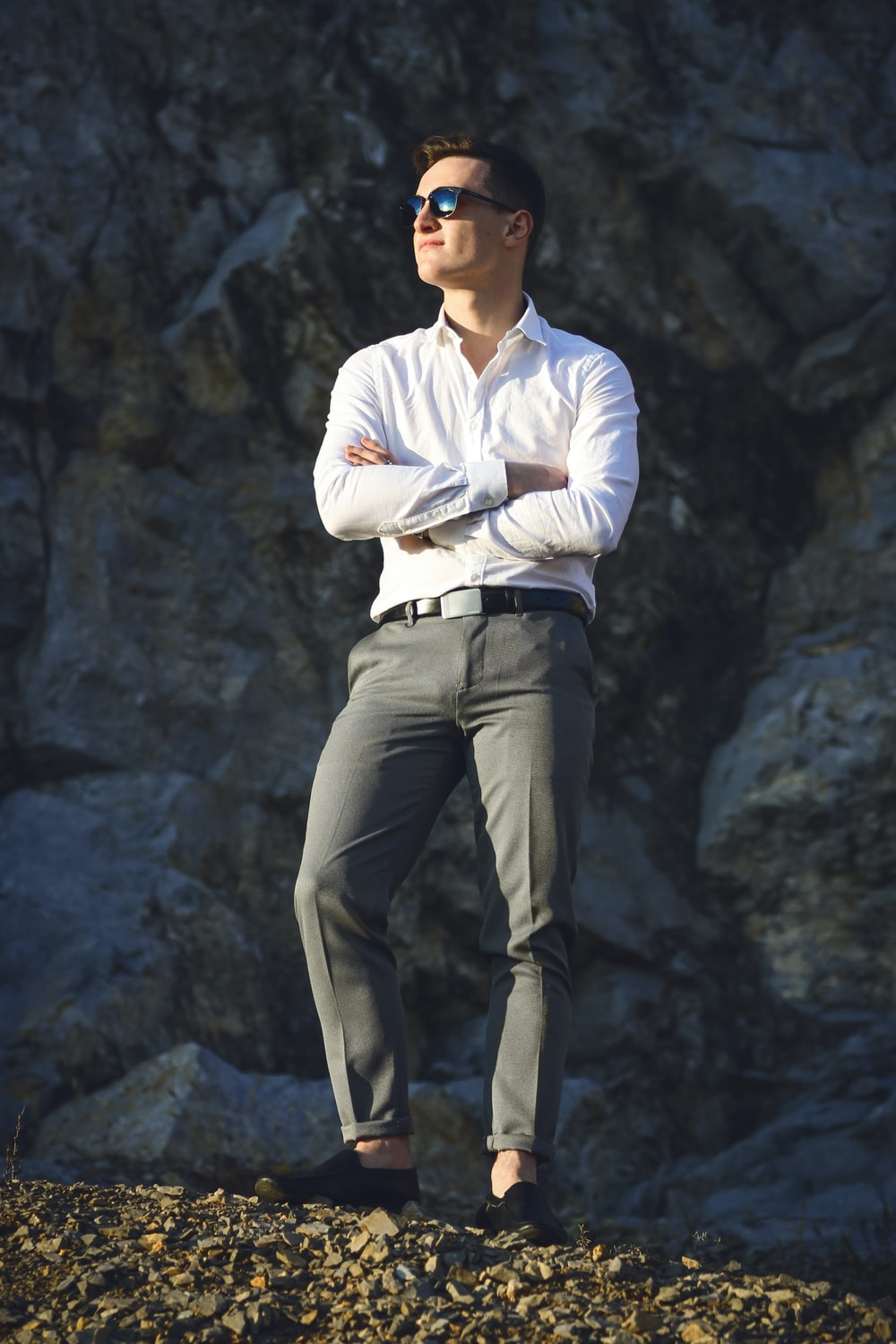 man in white dress shirt and gray pants standing on gray rock