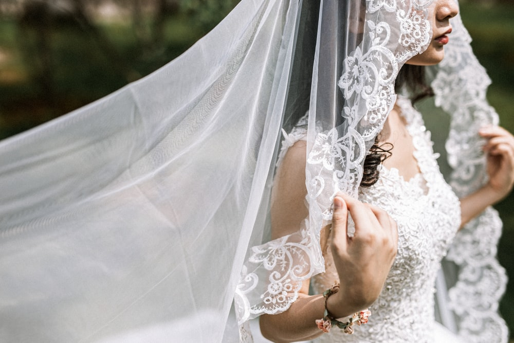 woman in white wedding dress holding white veil