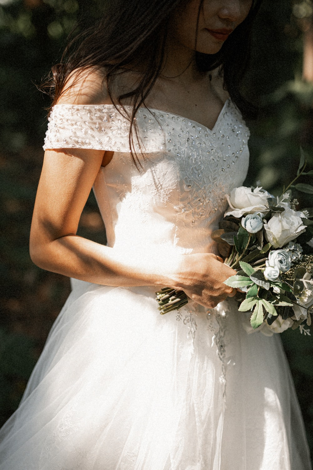 woman in white floral dress holding white flower bouquet