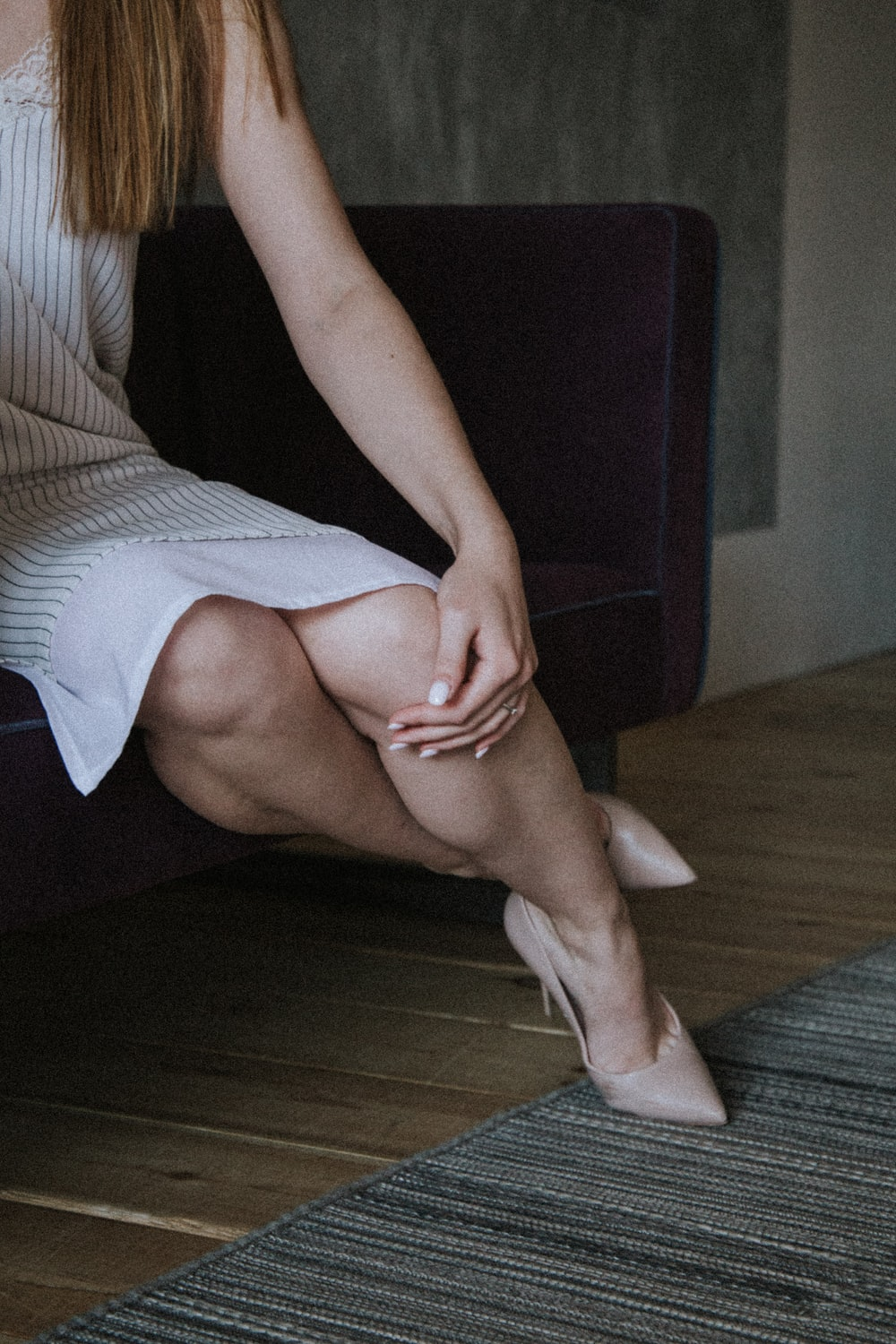 woman in black tank top and white skirt sitting on brown wooden floor