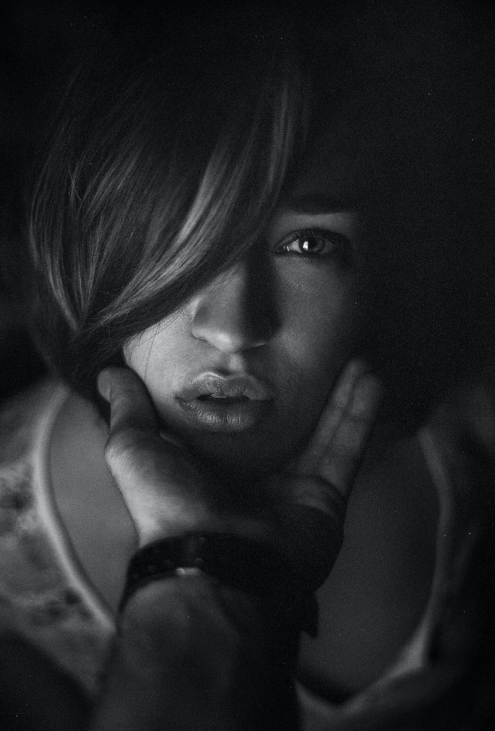 grayscale photo of woman with hand on her face