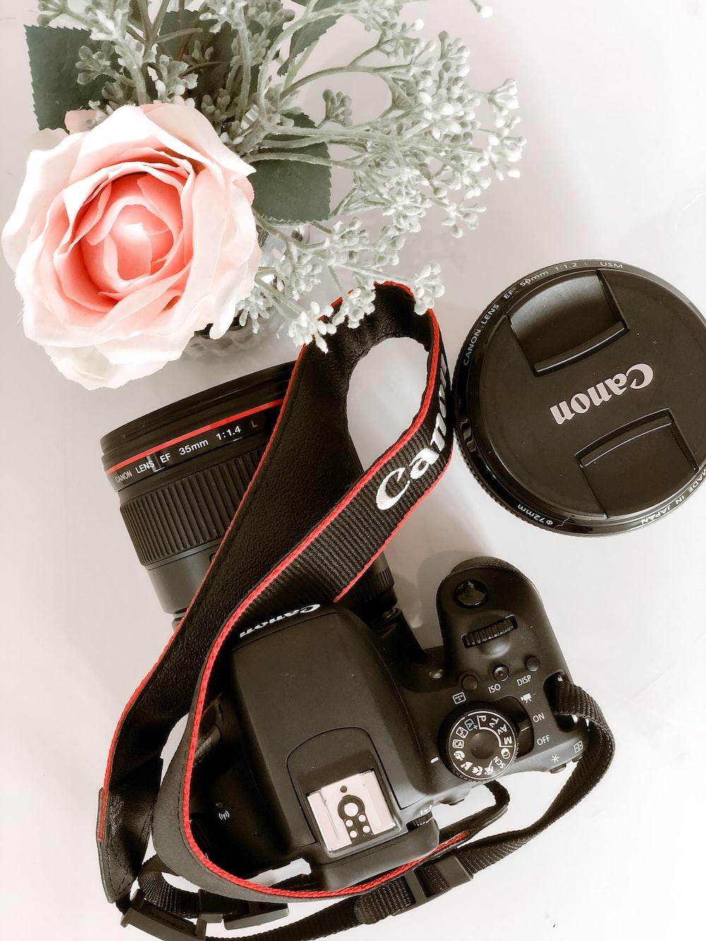 black and red nikon dslr camera on white floral textile