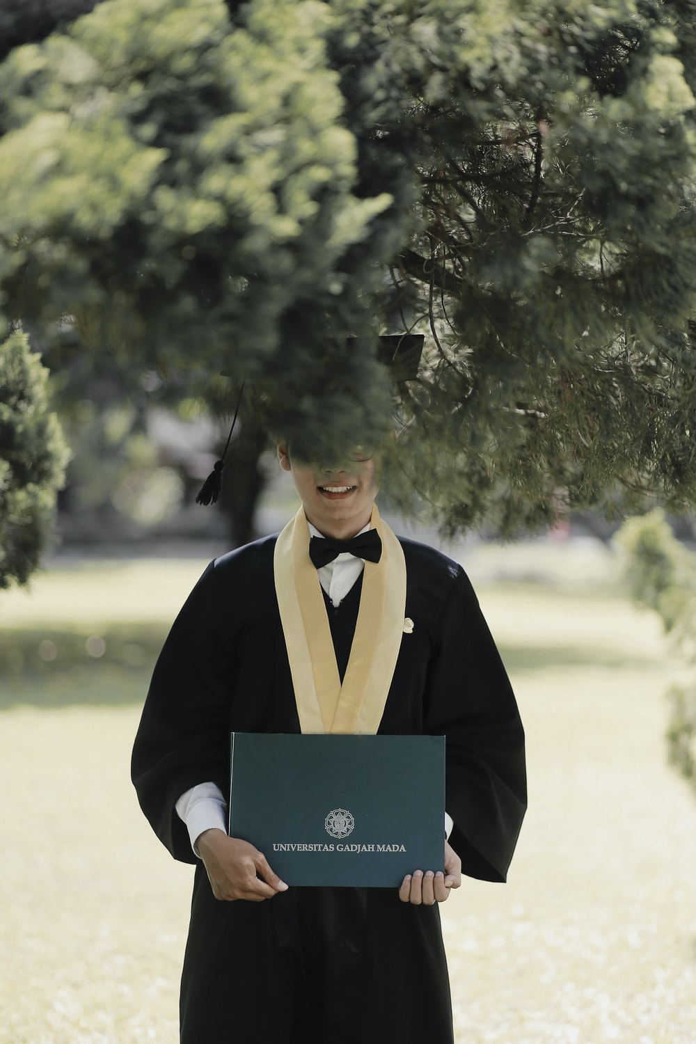 man in black academic gown holding blue paper