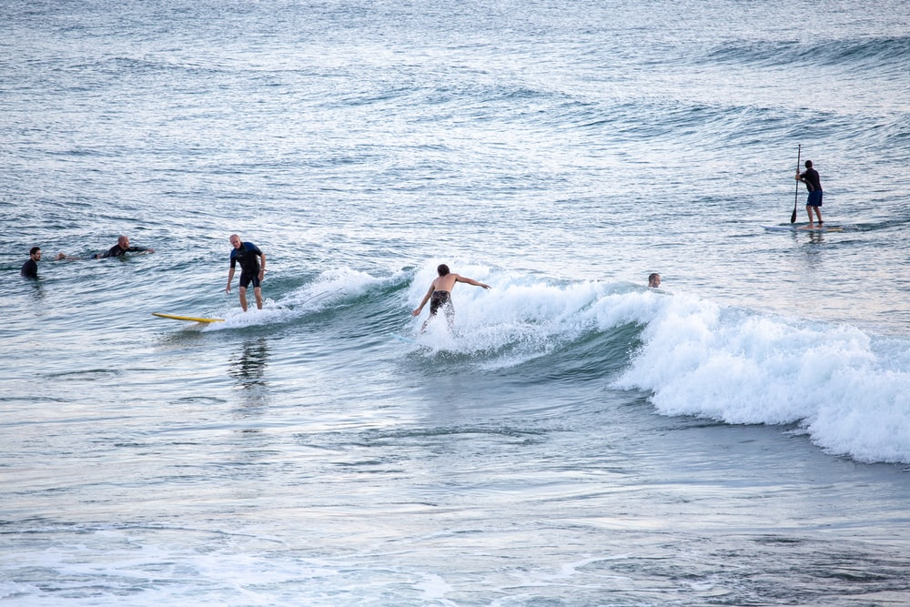 2 men surfing on sea waves during daytime
