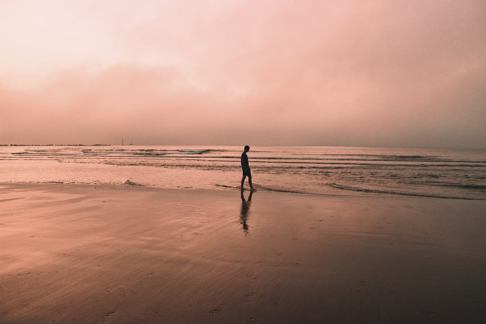 silhouette of person walking on beach during sunset