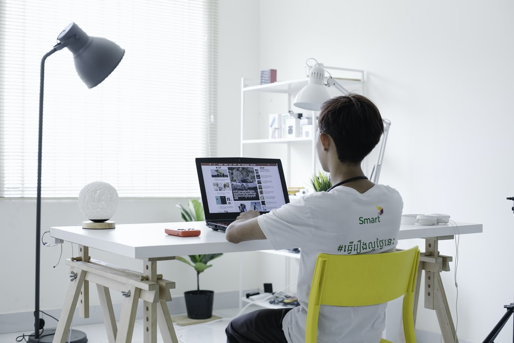 woman in white shirt sitting on chair using laptop computer