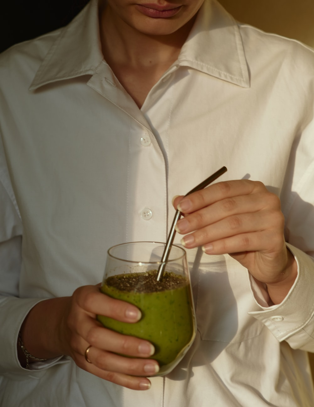 person in white button up shirt holding clear drinking glass with green liquid