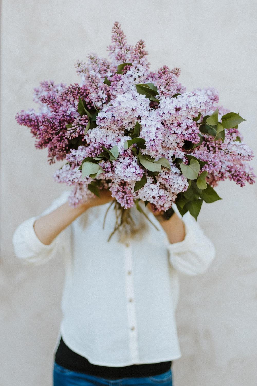 person holding purple flower bouquet