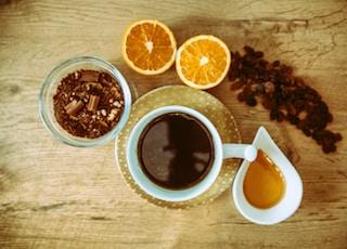 white ceramic mug with brown liquid and sliced orange