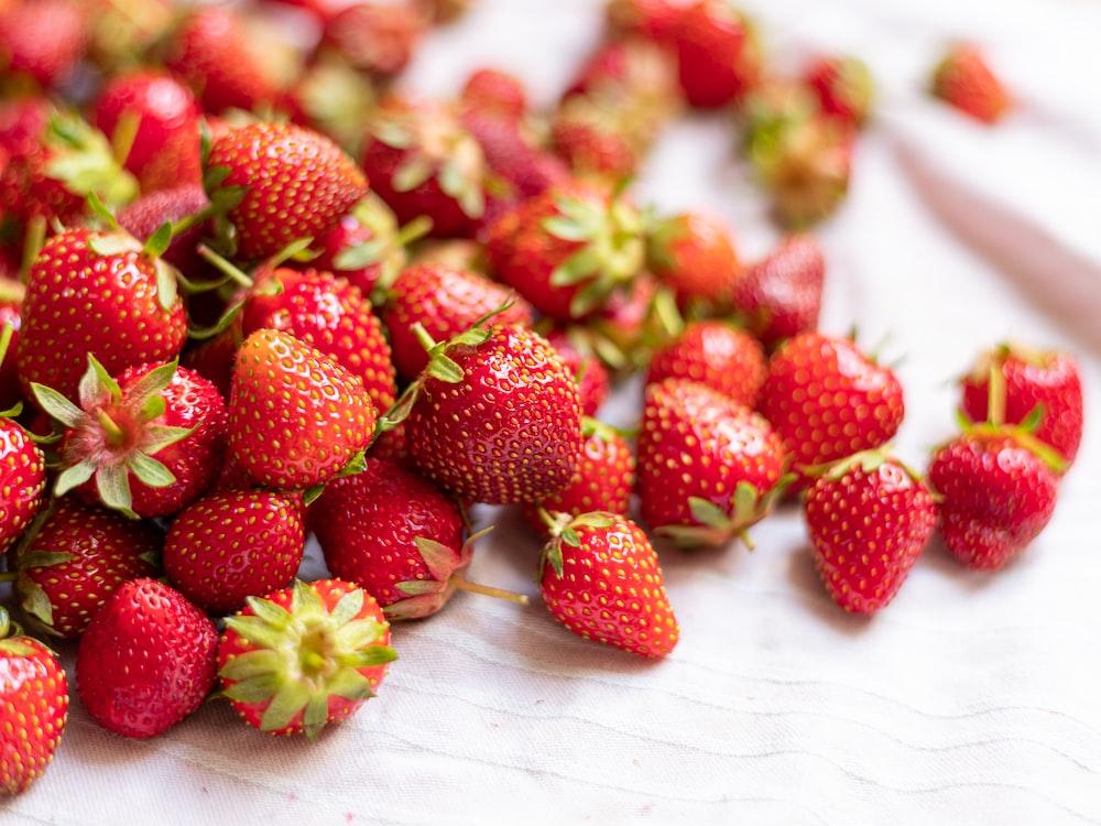 strawberries on white textile during daytime
