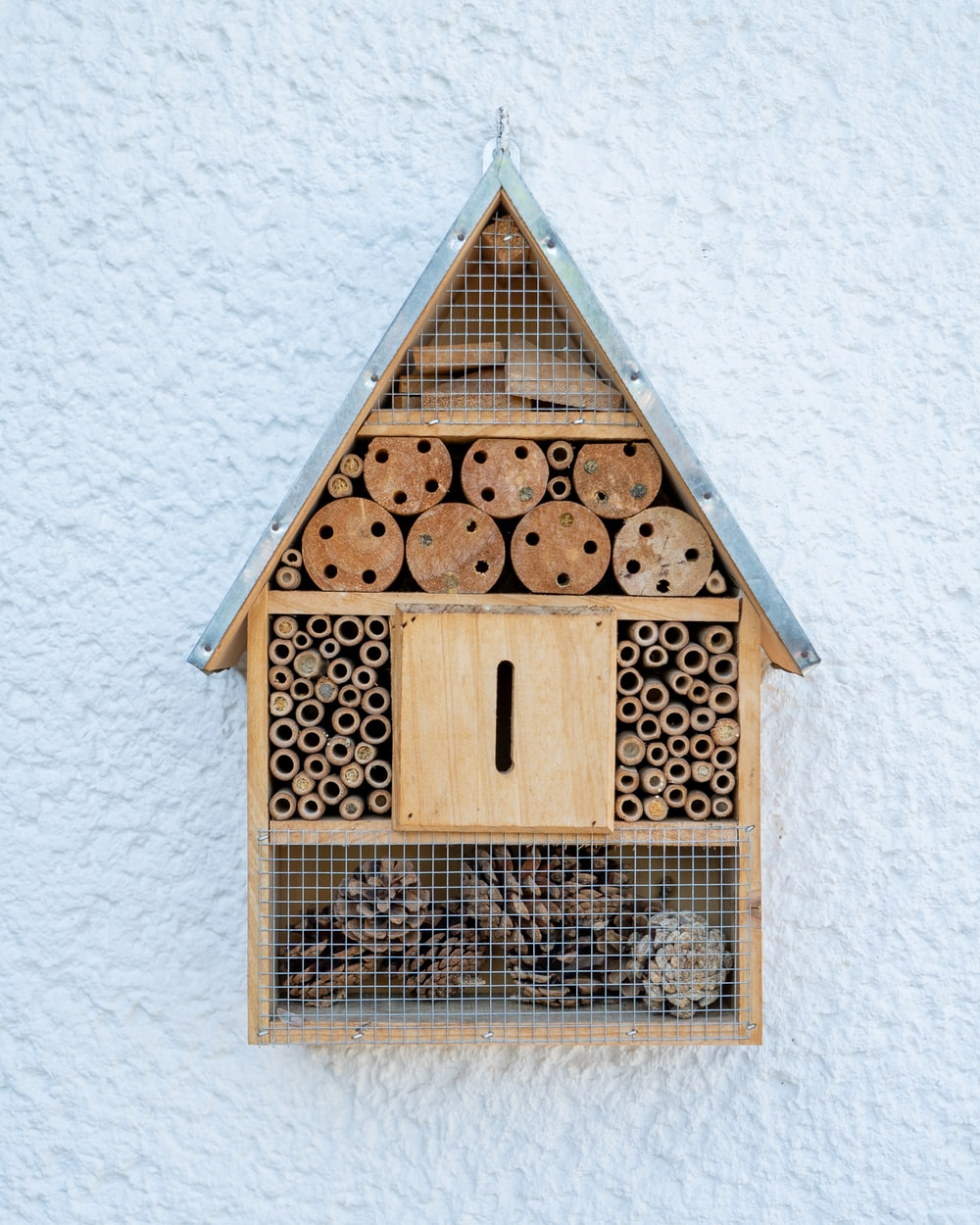 brown wooden bird house on white wall