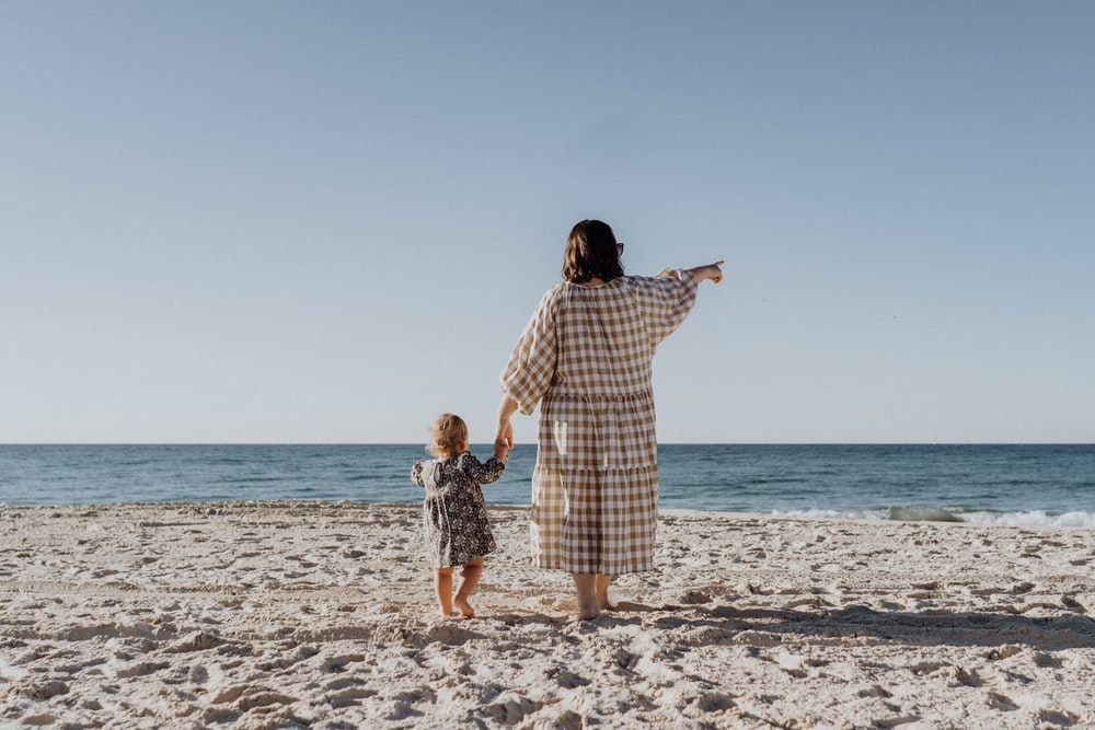 woman in white and black plaid dress standing on beach during daytime