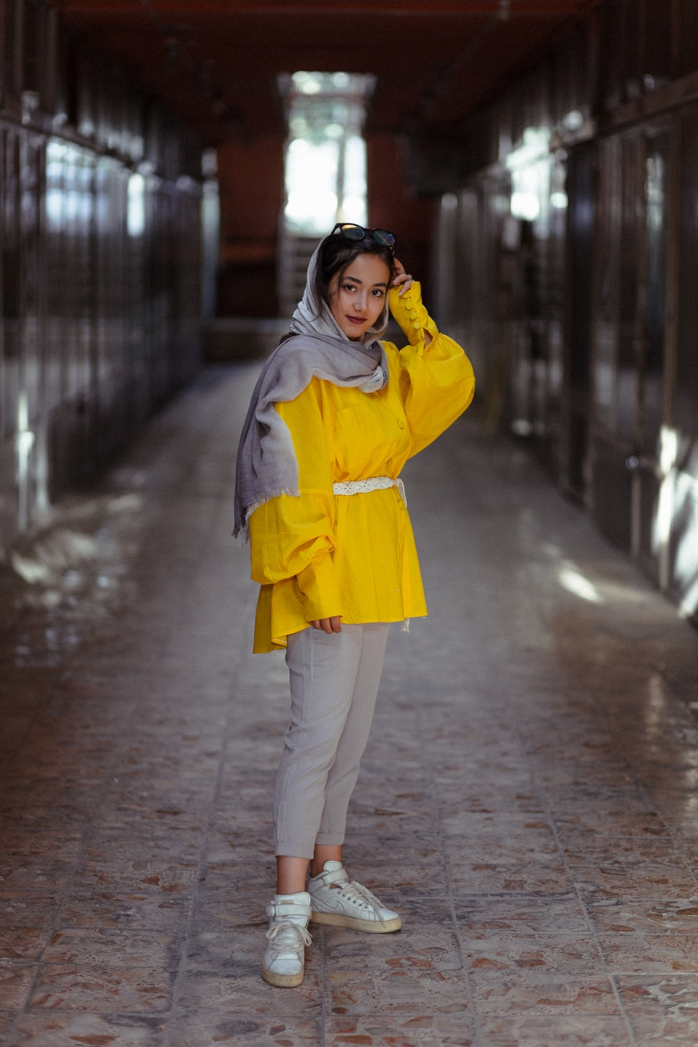 woman in yellow coat and white pants standing on sidewalk during daytime