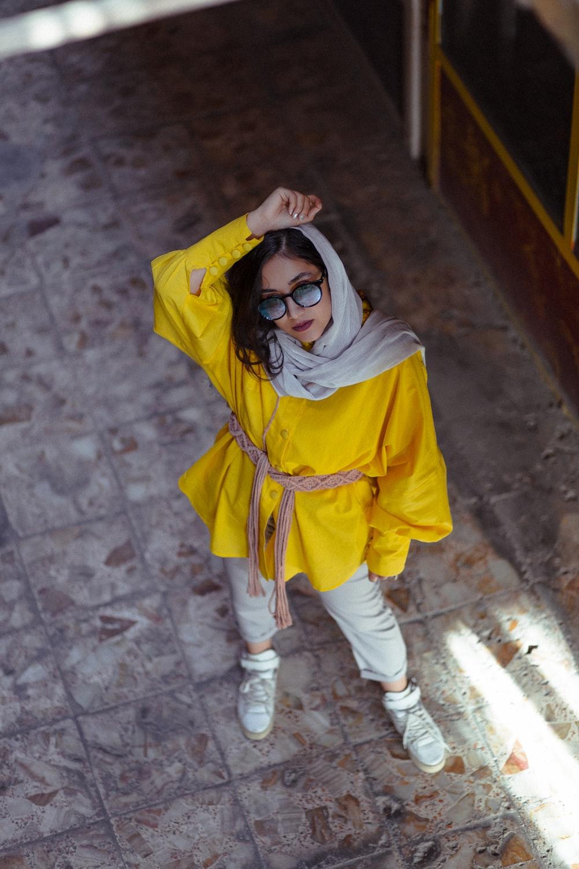 girl in yellow hoodie wearing black framed eyeglasses