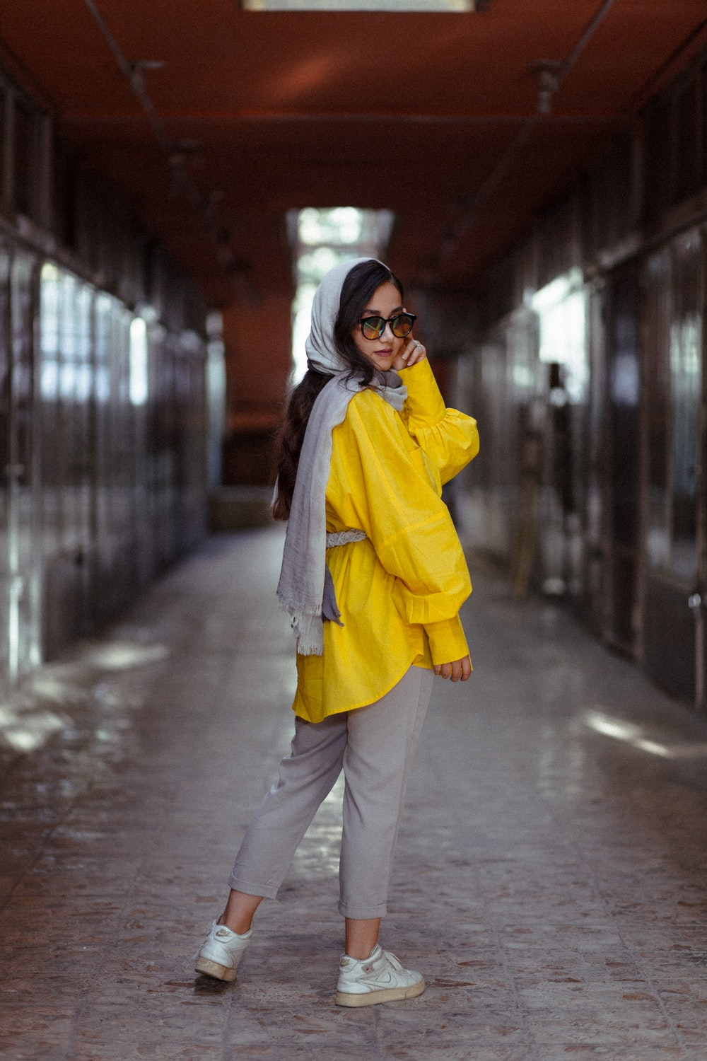 woman in yellow coat and black pants standing on sidewalk during daytime