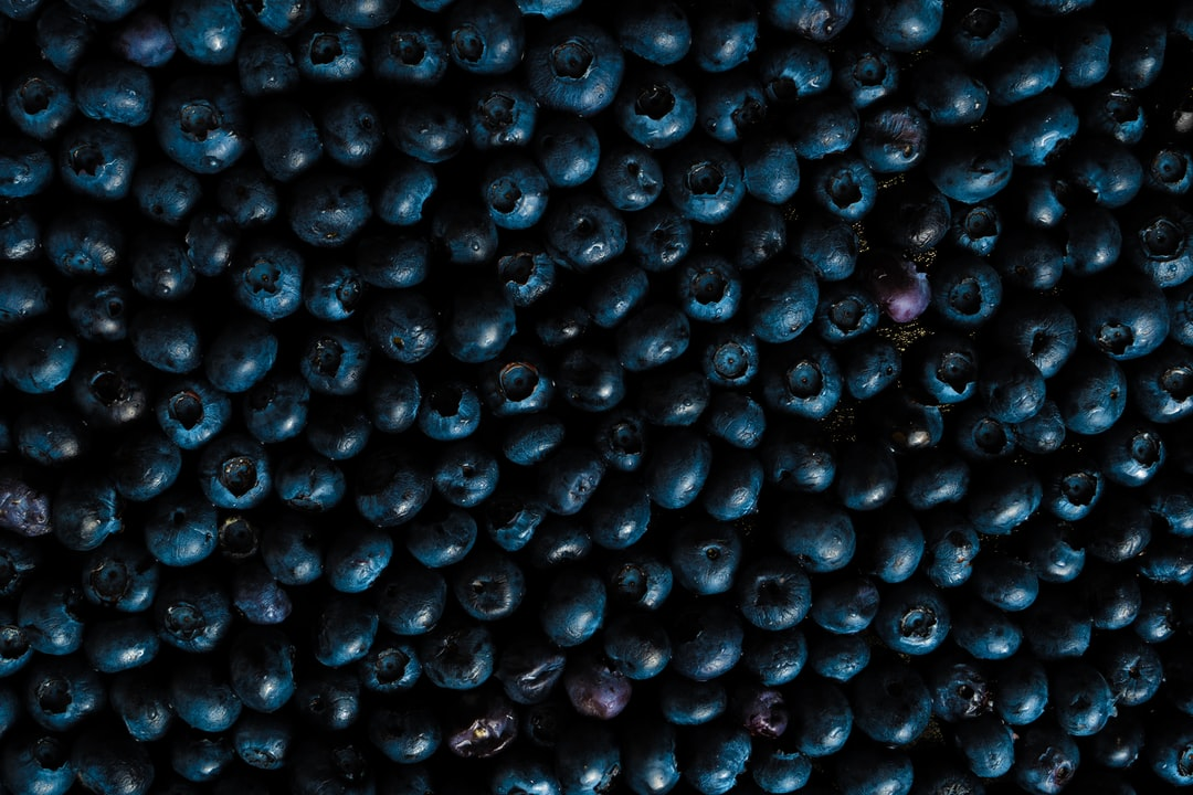 Black Round Fruits On White Surface - unsplash