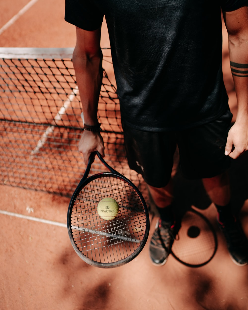 person in black shorts holding green tennis racket