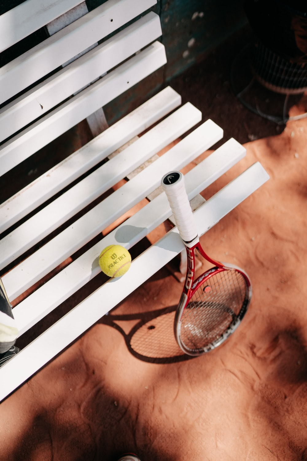 yellow tennis ball on brown wooden bench
