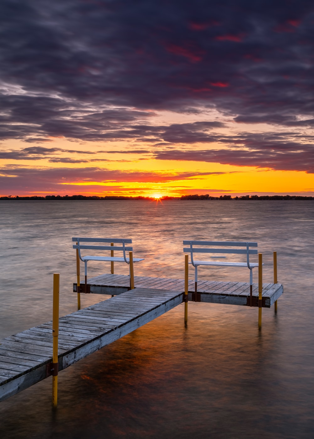 brown wooden dock on sea during sunset
