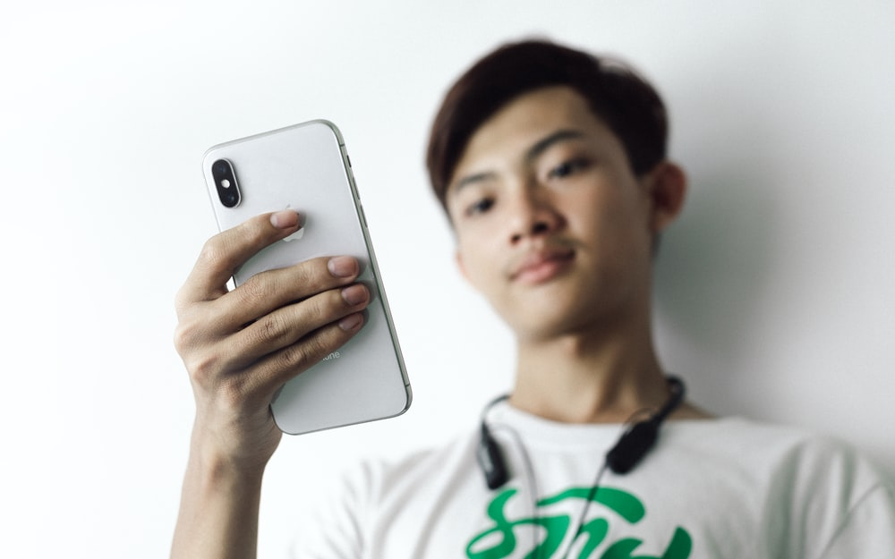 man in white crew neck shirt holding silver iphone 6