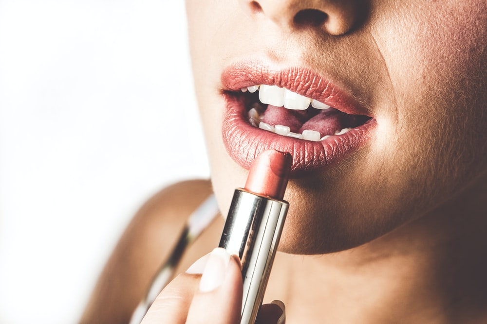 woman with red lipstick holding lipstick