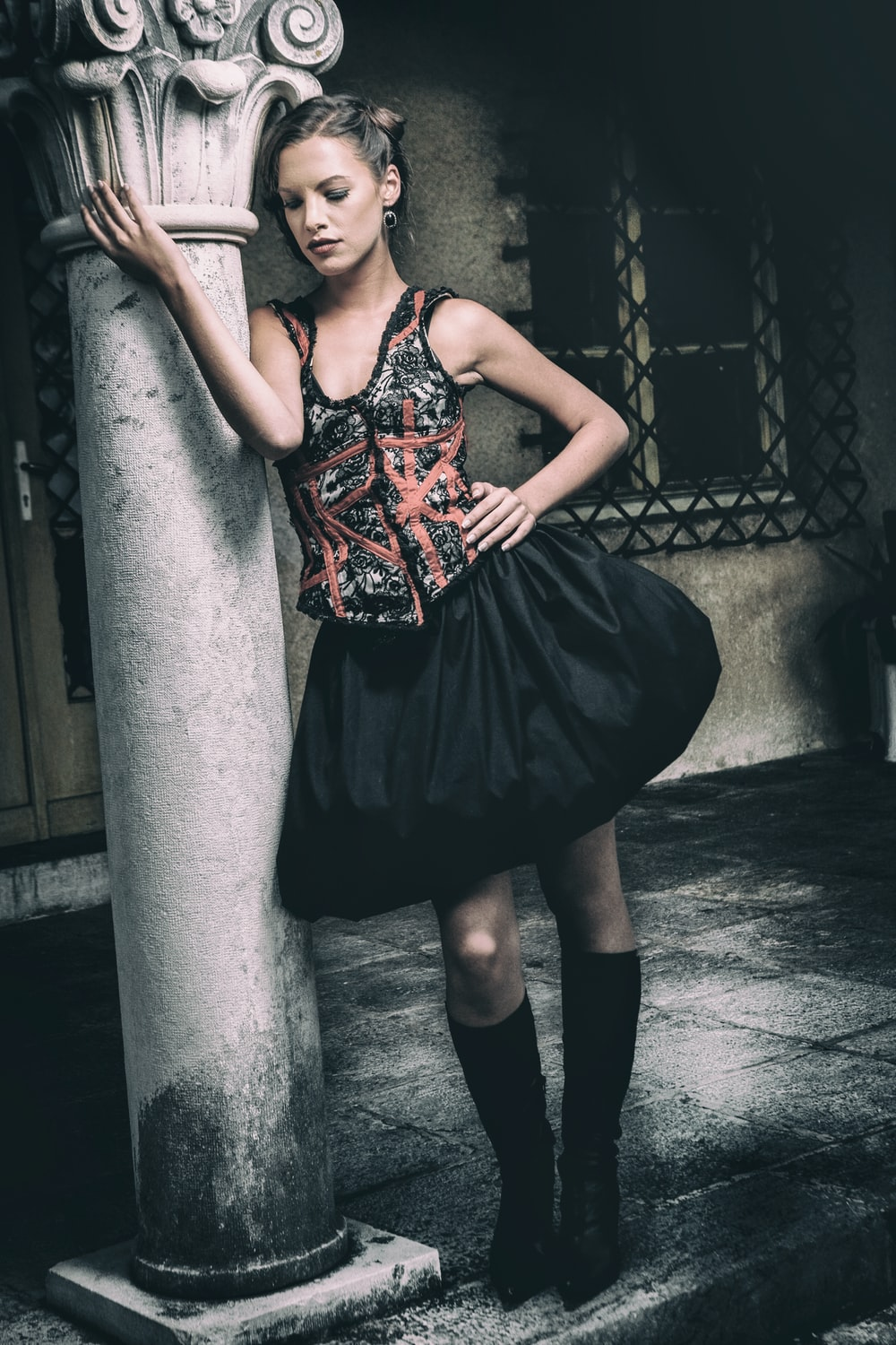 woman in black and red spaghetti strap dress leaning on gray concrete post