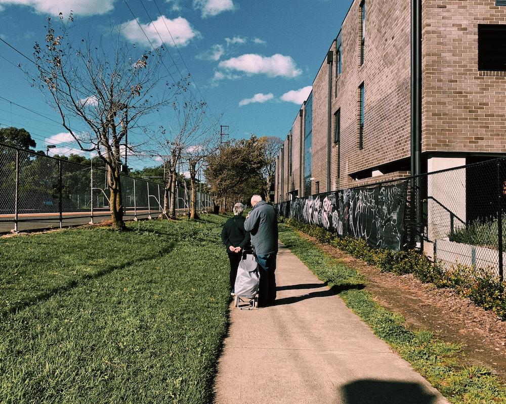 man in gray jacket walking on pathway during daytime