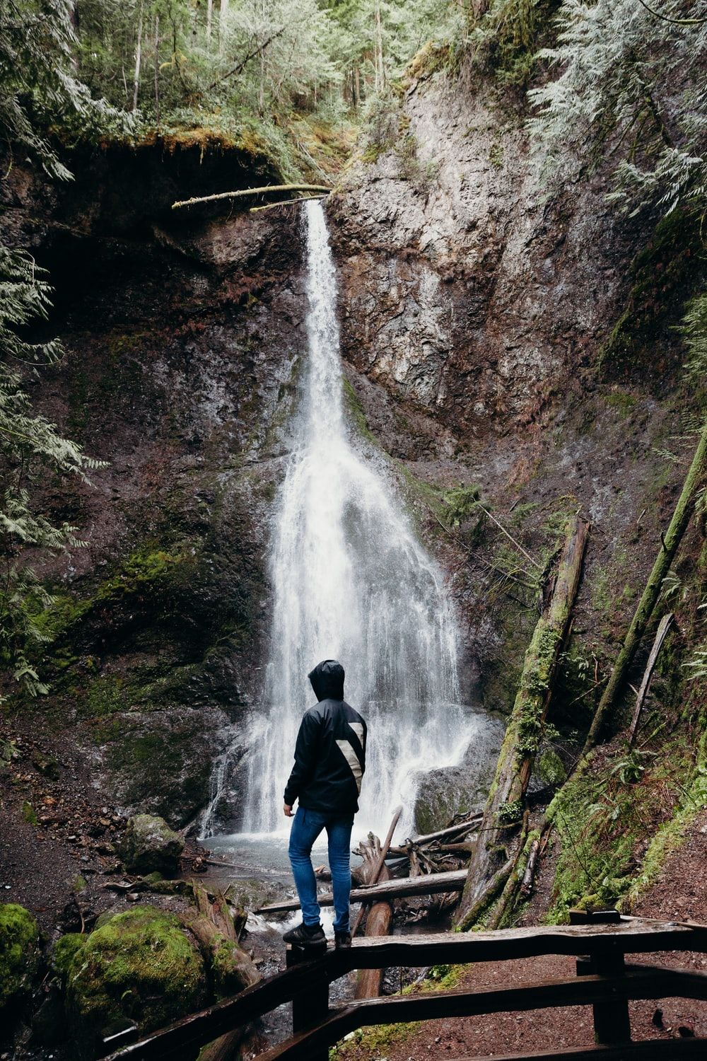 man in black jacket standing in front of waterfalls during daytime