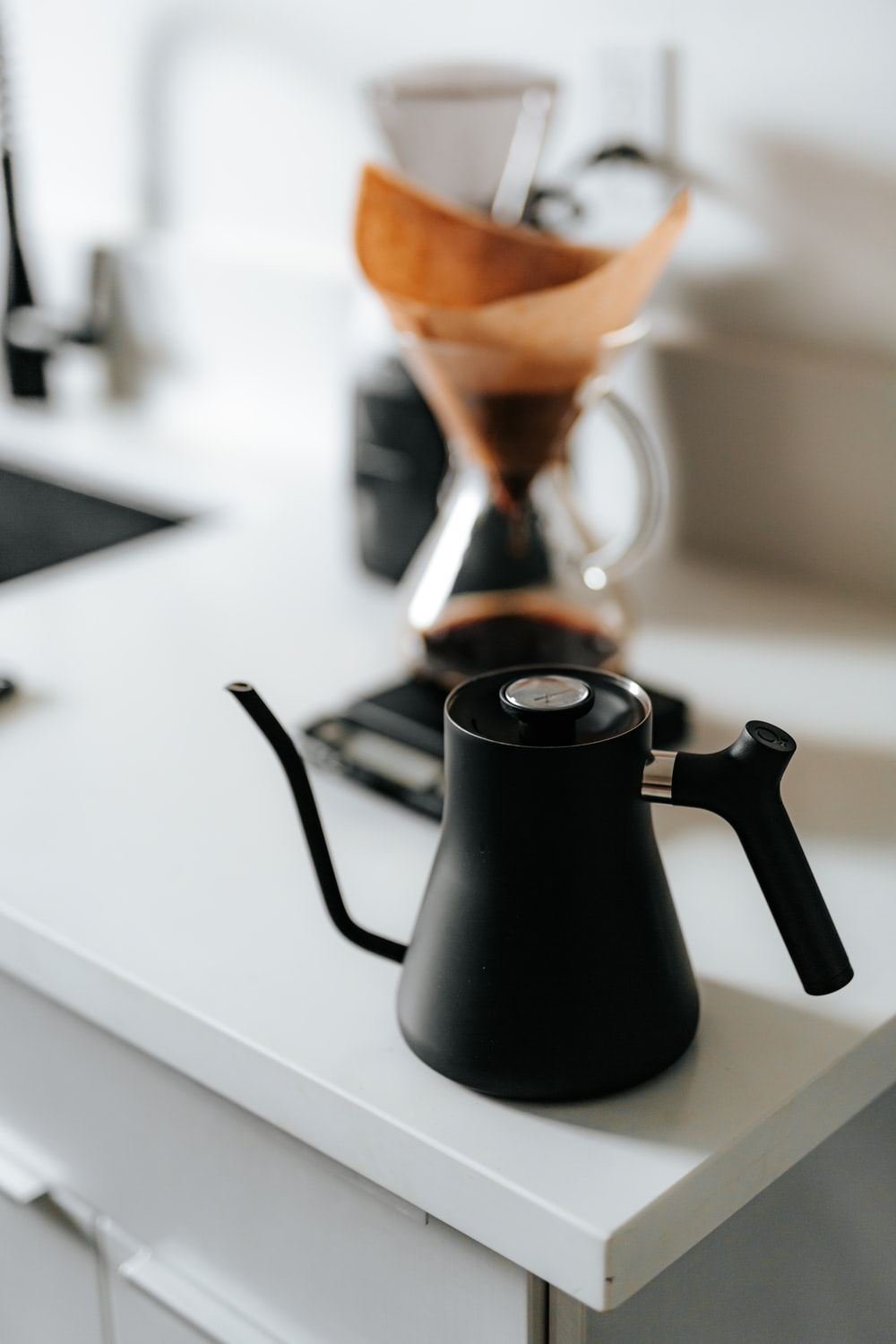 black ceramic teapot pouring brown liquid on black ceramic mug