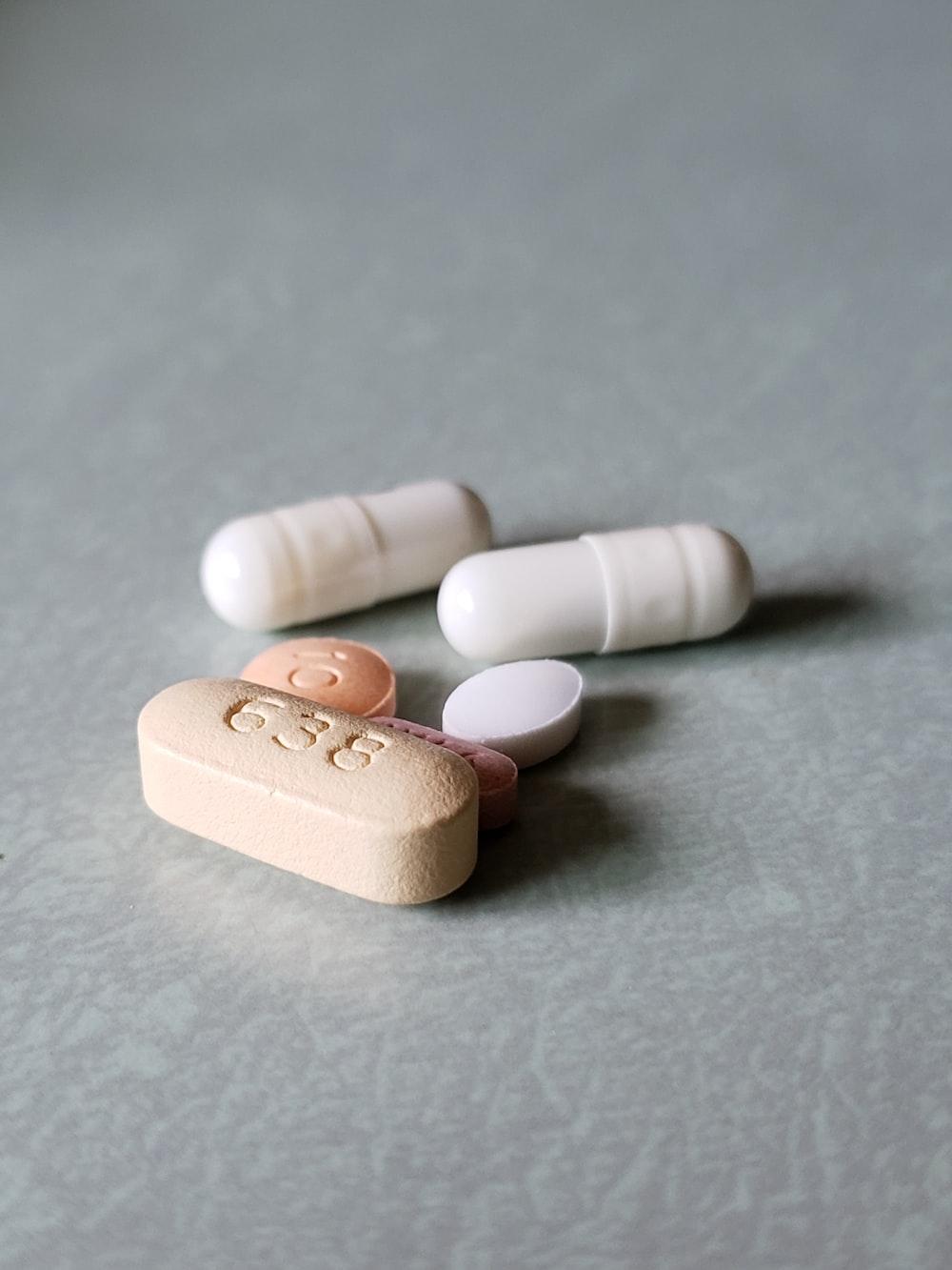 white medication pill on gray textile