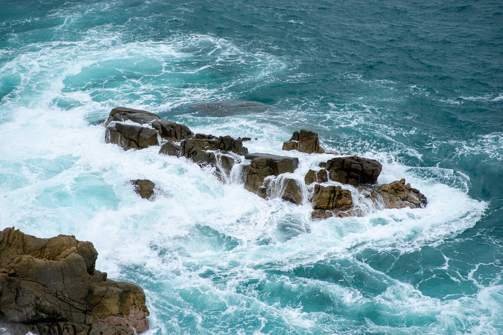 brown rocky shore with ocean waves during daytime