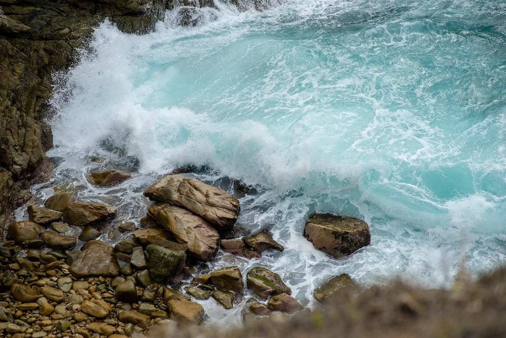 brown rocks on body of water during daytime