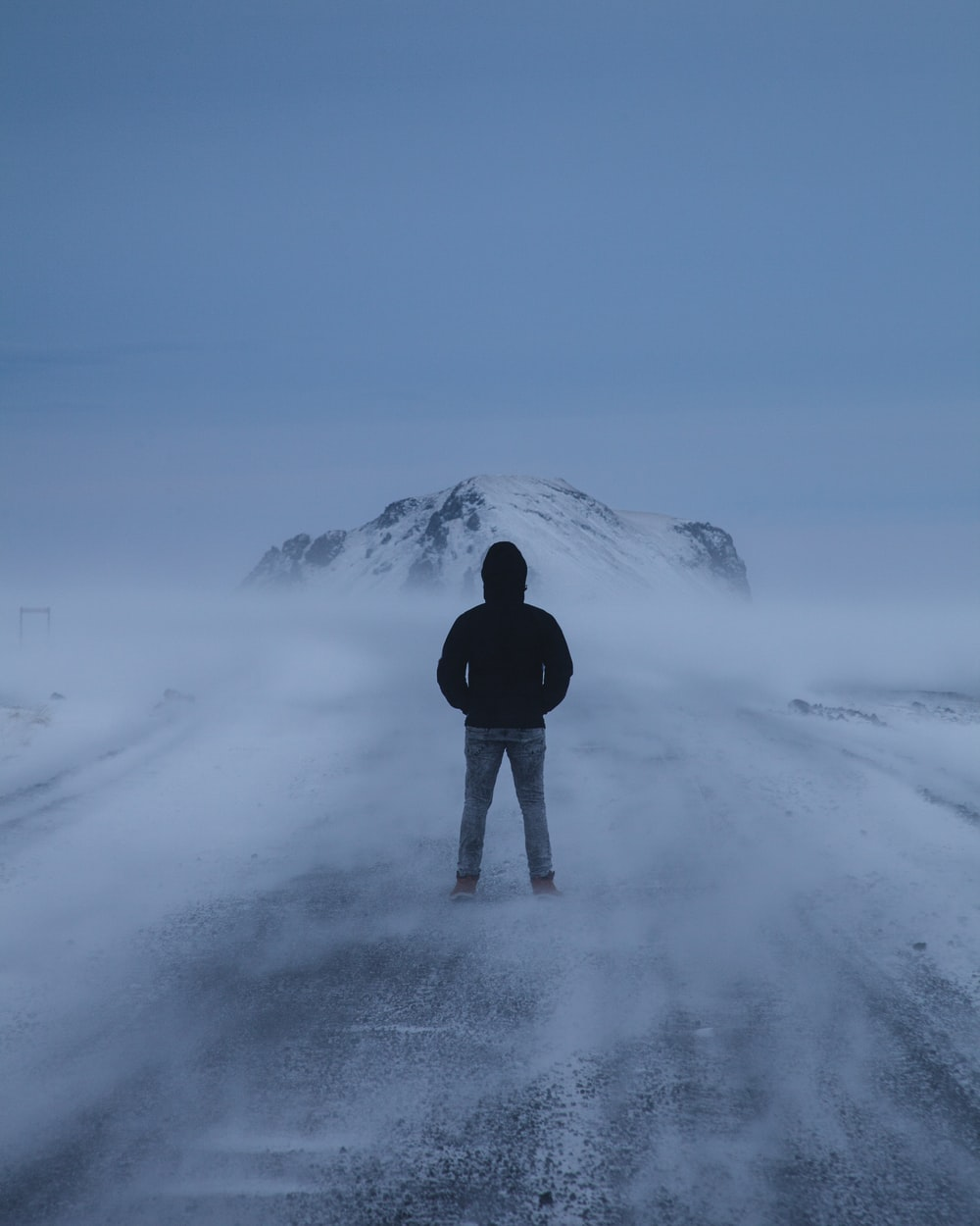 person in black jacket standing on snow covered ground during daytime