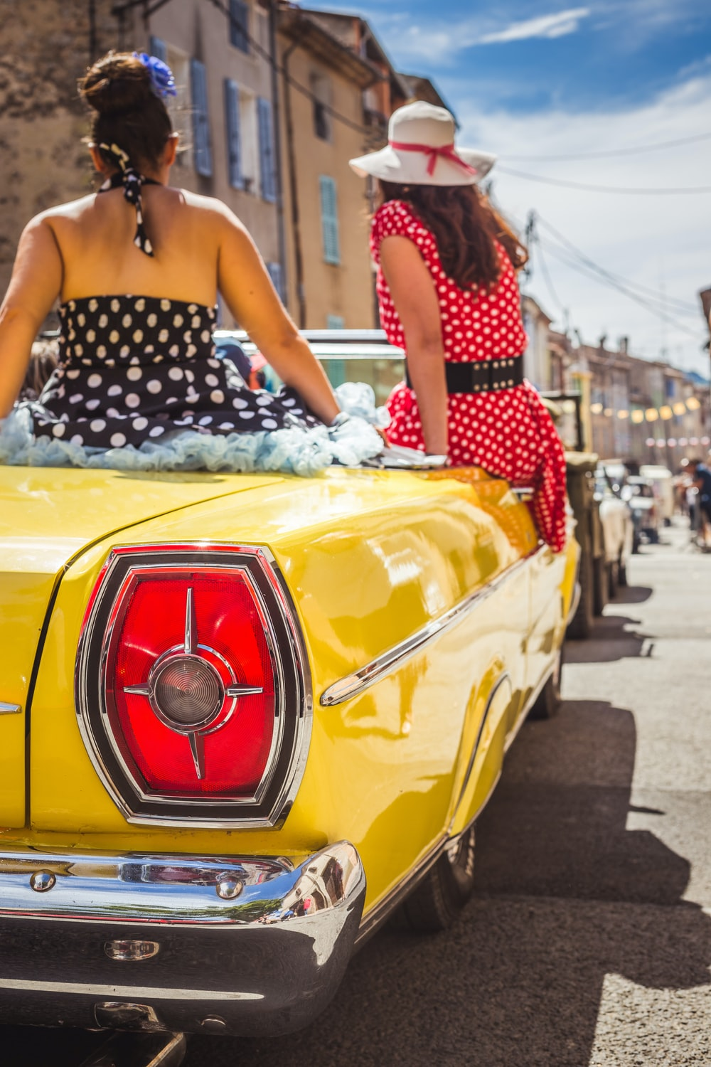 woman in black and white polka dot dress sitting on yellow car hood during daytime