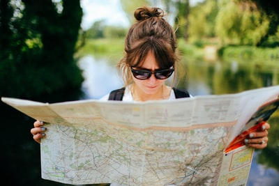 woman in black sunglasses and white shirt map teams background